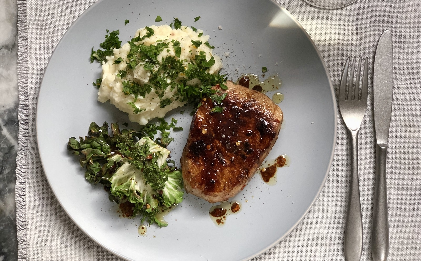 Grilled pork loin steaks with greens and balsamic glaze